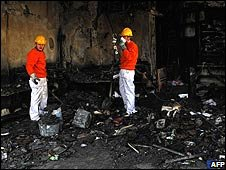 Greek workers clear up a shop burnt in rioting in the northern city of Thessaloniki (11/12/2008)