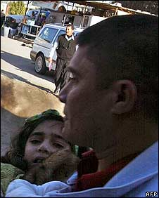 A man carries an injured girl from the scene of the blast