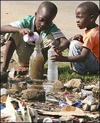 Niños llenando una botella de plástico con agua sucia.