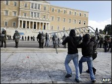 Greek youths attack riot police with a steel fence outside parliament in Athens on 12 December