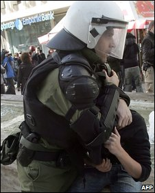 A Greek riot policeman arrests a youth near parliament in Athens on 12 December