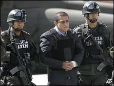 Police officers escort Diego Montoya (centre) in Bogota, Colombia, 12 December 2008