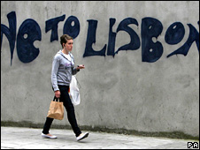 "A woman walks past graffiti urging a ""No"" vote in the Lisbon Treaty referendum (9 June 2006)"