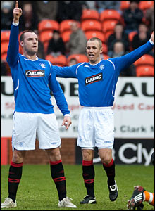 However the Rangers striker opens the scoring moments later and celebrates with team-mate Kenny Miller (right)