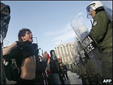 A youth bares his chest to riot police