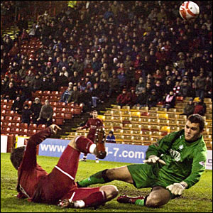 Lee Miller (left) guides his effort goalward to extend Aberdeen's advantage to two goals