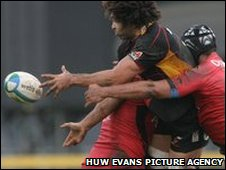 Colin Charvis is tackled by Toulouse's Thierry Dusautoir and Shaun Sowerby