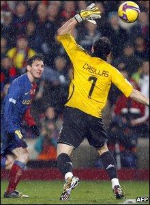 Lionel Messi scores over the head of Iker Casillas