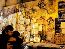 A man comforts a woman in front of messages left by people at the site where Alexandros Grigoropoulos was shot dead (14 December 2008)