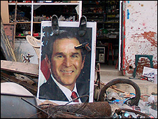 Bush poster in Khiam, south Lebanon, adorned with shoes and toy gun (Photo by Martin Asser, August 2006)
