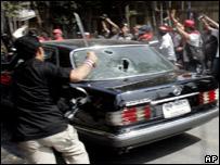 Manifestantes rompen el cristal de un auto