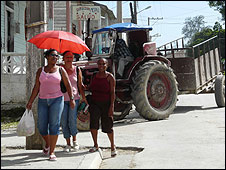 People walk through Manuel Tames, Cuba