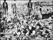 Men stand besides the skulls and corpses of Armenian victims of the Turkish deportation circa 1915