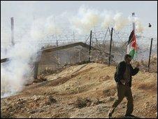 A protestor runs from an Israeli tear gas grenade in Bilin on 12/12/2008