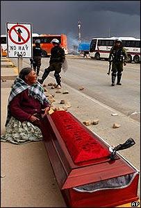 Mujer sentada junto al ata�d de quien muri� en el enfrentamiento