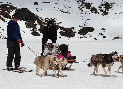 What a way to travel! Graham is given a lift by the husky dogs in New Zealand