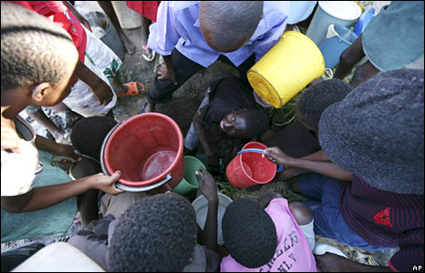 Women and children wait to get water from an underground source, following a water cut in Harare. (Tsvangirayi Mukwazhi/AP - 1 December 2008)