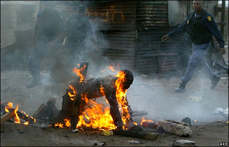 Policemen attend to a man that was set alight in Reiger Park in Johannesburg during xenophobic clashes. (Photo: AFP - 18 May 2008)