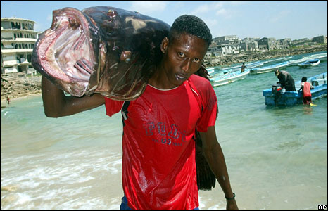 A Somali fisherman carries his catch in the capital, Mogadishu (Photo: Mohamed Sheikh Nor/AP - 22 November 2008)