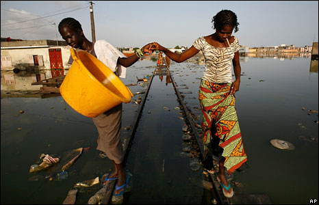Girls hold hands to keep their balance as they walk the rails of flooded train tracks in Thiaroye Sur Mer, on the outskirts of Dakar, Senegal. (Photo: Rebecca Blackwell/AP - 10 September 2008)