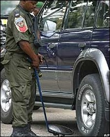 Nigerian policeman checking under car for bombs