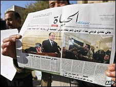 Iraqi journalists hold a newspapers during a protest outside the Union of Iraqi Journalist headquarters.