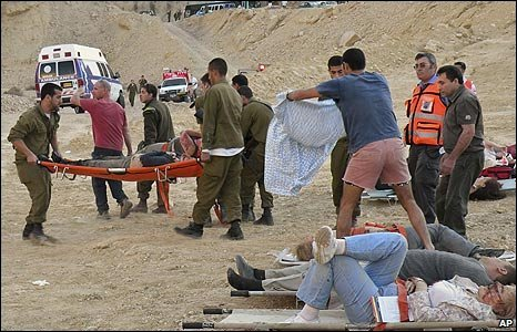 Medical workers carry wounded people away from the scene of a bus crash in southern Israel