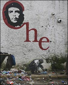 A homeless man rummages through rubbish by a wall adorned with Che's image