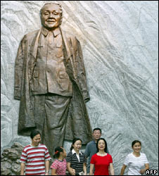 Tourists next to a statue of Deng Xiaoping