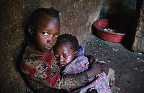 Zimbabwean youngster, seven year-old Sinikiwe cradles her three-year-old brother Simba at their home. Picture by Tearfund.