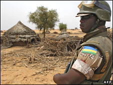 A Rwandan African Union soldier surveys an abandoned village in Darfur in June 2006