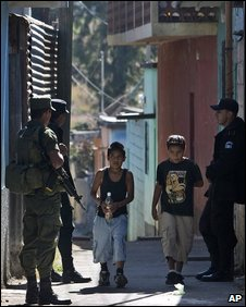 Children walk past soldiers and a police officer who patrol the slum of El Milagro, in Mixco, Guatemala on 2 December