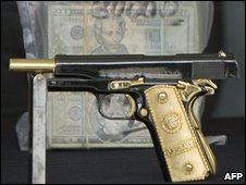Mexican police display the customized gold-plated handgun of an alleged  founder of the hitmen alled the Zetas in Novmber 2008