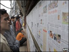 Bangladeshi men read newspapers pasted on a wall in Dhaka