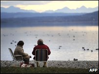 An elderly couple sitting next to a lake