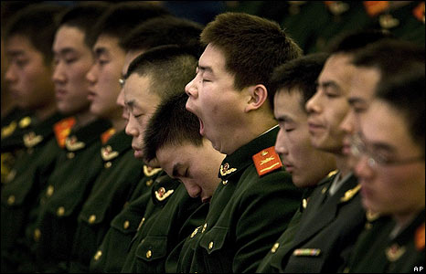 Chinese paramilitary police officers doze at the Great Hall of the People in Beijing