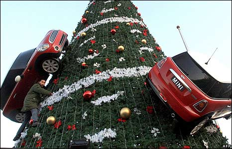 A Chinese worker decorates a Christmas tree with mock Mini Cooper cars