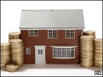 Model house with stacks of pound coins