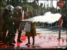 A woman walks past police using tear gas in Athens (18 December 2008)