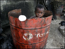 A child playing in an oil drum