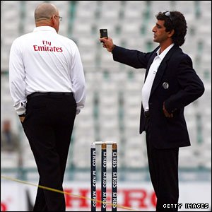 Asad Rauf brandishes his light meter at fellow umpire Daryl Harper
