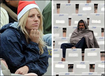 An England fan wearing a Santa hat and an Indian fan watch the game