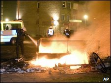 A police officer tries to extinguish burning barricades