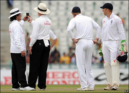 Umpires Asad Rauf and Daryl Harper consult their light meters