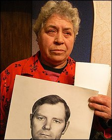 Woman shows a picture of  husband kileld in a mine