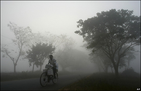 A cyclist makes his way through fog on the outskirts of Bhubaneswar, India