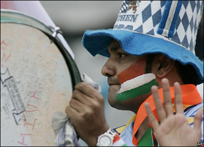 An Indian fan with a drum and the national flag painted on his cheek