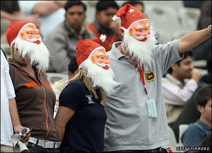 Three England supporters in Santa Claus masks cheer on their team