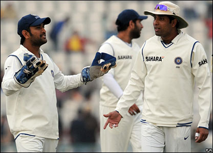 India captain Mahendra Dhoni (left) gestures as play ends early on day two