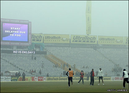 Players warm up in the fog after the start is delayed